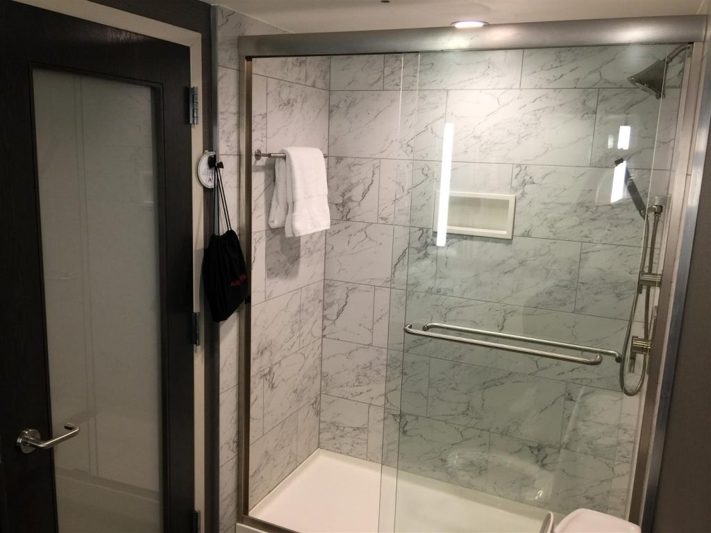 The marble shower looks very enticing with its glass doors.