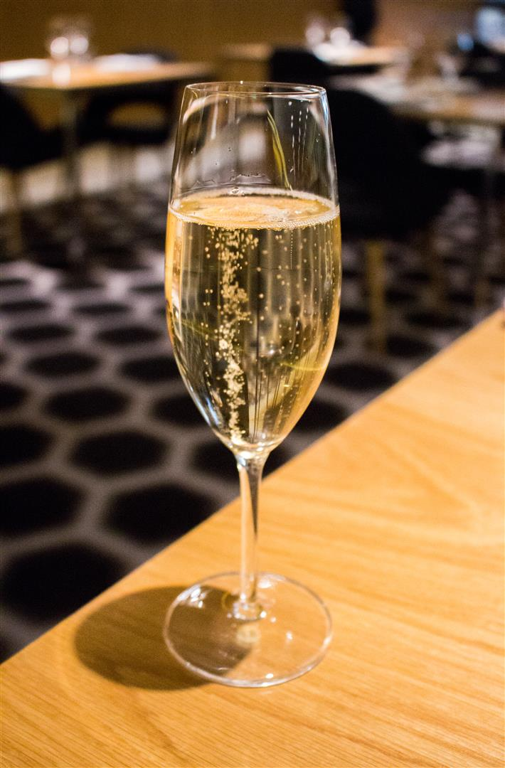 You can order anything from the bar at the dining room tables as well. Try the champagne!